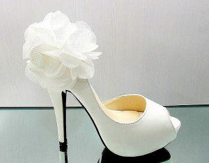 Белые свадебные туфли украшенные нежным цветком.